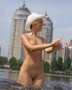 Кудрявая блондинка позирует голая в речке и на тёплом песке