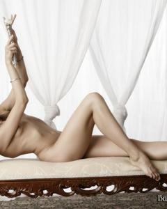 Длинноногая модель принимает эротичные позы на винтажной кушетке