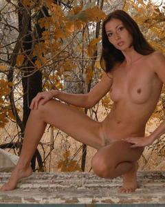 Худая девушка позирует голышом у окна на фоне осенних пейзажей