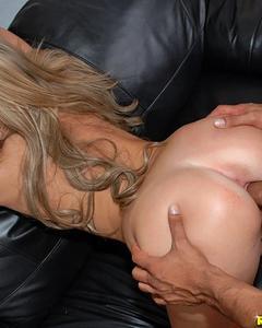 Улыбчивая девушка с маленькой грудью дает раком на кожаном диване