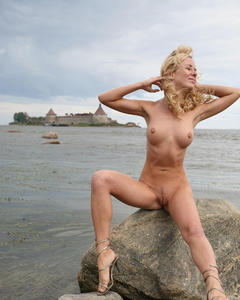 Кучерявая блондинка показывает пизду на морских камнях