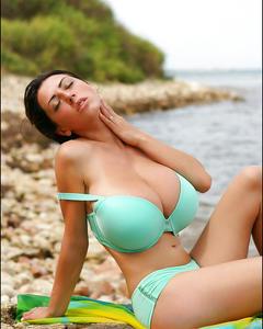 Брюнетка оголяет огромные дойки на берегу моря