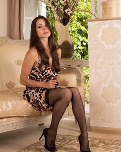 Сексуальная мамочка играет с бритой киской на удобном диване
