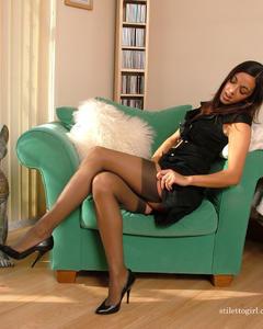 Сексуальная девушка в черных чулках снимает одежду в кресле