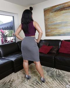 Негритянка в серой юбке показывает крупную попку на чёрном диване