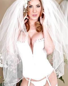 Невеста за тридцать в белых чулках снимает платье около зеркала
