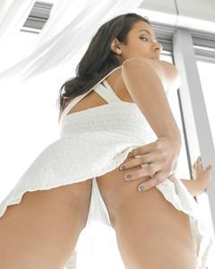 Спортивная мулатка сидит на белой кровати и раздвигает ножки на камеру