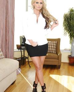 Блондинка с большой грудью позирует на замшевом диване