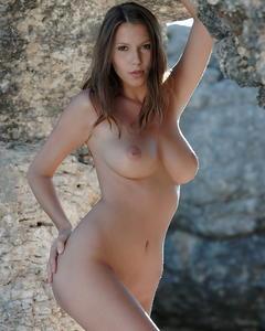 Грудастая девушка демонстрирует тело на фоне скал