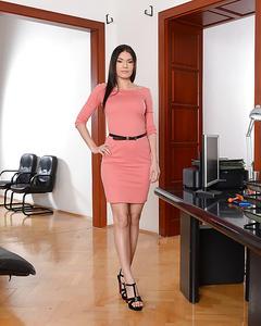 Брюнетка на высоких каблуках позирует в офисе мужа