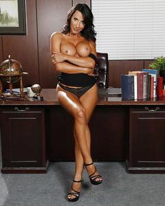 Горячая работница офиса демонстрирует большие сиськи у стола