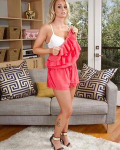 Блондинка Эмили Остин с пирсингом в сосках показывает киску на сером диване