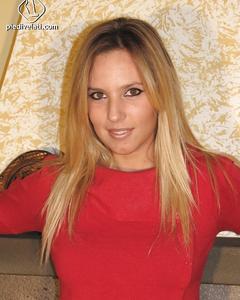 Блондинка демонстрирует ножки, сидя на полу своей комнаты