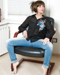 Плоская девушка широко расставляет ноги, сидя на кожаном кресле