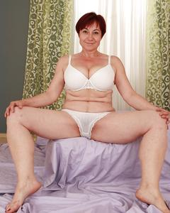 Зрелая тётка в очках показывает тело в спальне