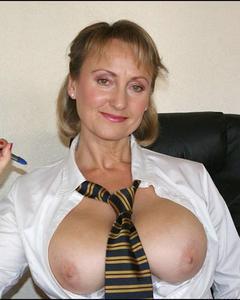 Зрелка демонстрирует пышную грудь и голую вагину на рабочем месте