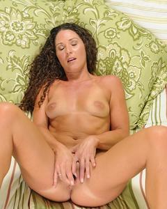 Кудрявая 33-летняя дамочка дрочит киску игрушкой на кровати