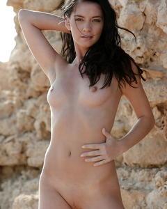 Молодая брюнетка позирует голая возле скал