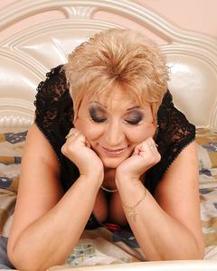 Зрелая блондинка в чёрных чулках позирует на двухспальной кровати