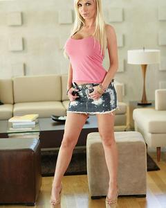 Блондинка медленно снимает розовую майку и оголяет огромную грудь