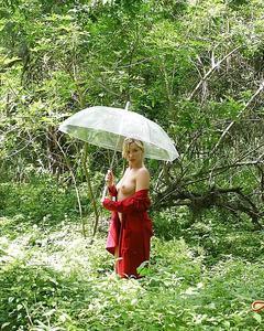 Обнаженная блондинка с зонтом позирует голой в дремучем лесу