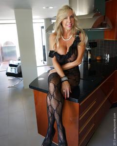 Зрелая блондинка в прозрачном наряде мастурбирует фаллосом на кухонном ковр ...