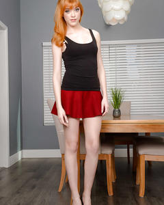 Рыжая девушка раздевается на столе кабинета