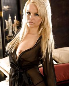 Красивая блондинка раздевается и позирует голая на кровати