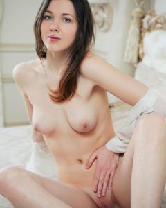 Брюнетка в белой рубашке показывает вагину на двухспальной кровати