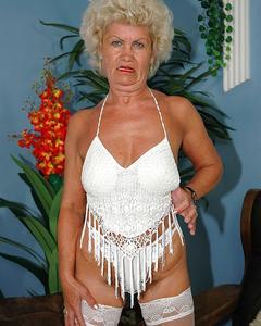 Похотливая бабушка в белых чулках показывает волосатую пизду дома