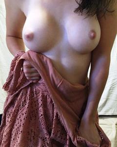 Девушка показывает свои сиськи и голую попку дома