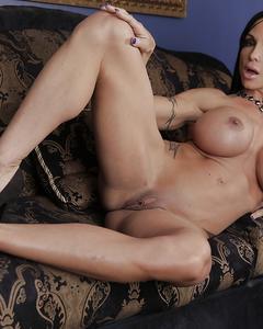 Татуированная бодибилдерша демонстрирует свои прелести на замшевом диване