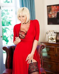 Зрелая женщина в сексуальном нижнем белье показывает стриптиз