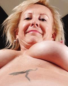 Зрелая блондинка демонстрирует тело на стареньком диване