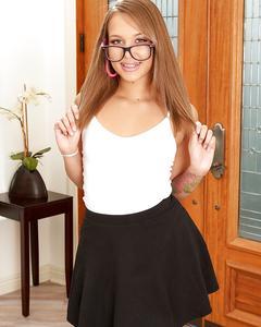 Liza Rowe в очках раздевается на фоне двери